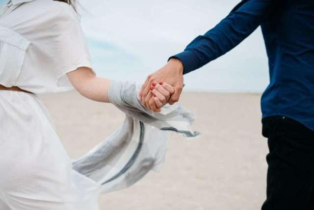 bračni par se drži za ruke na plaži