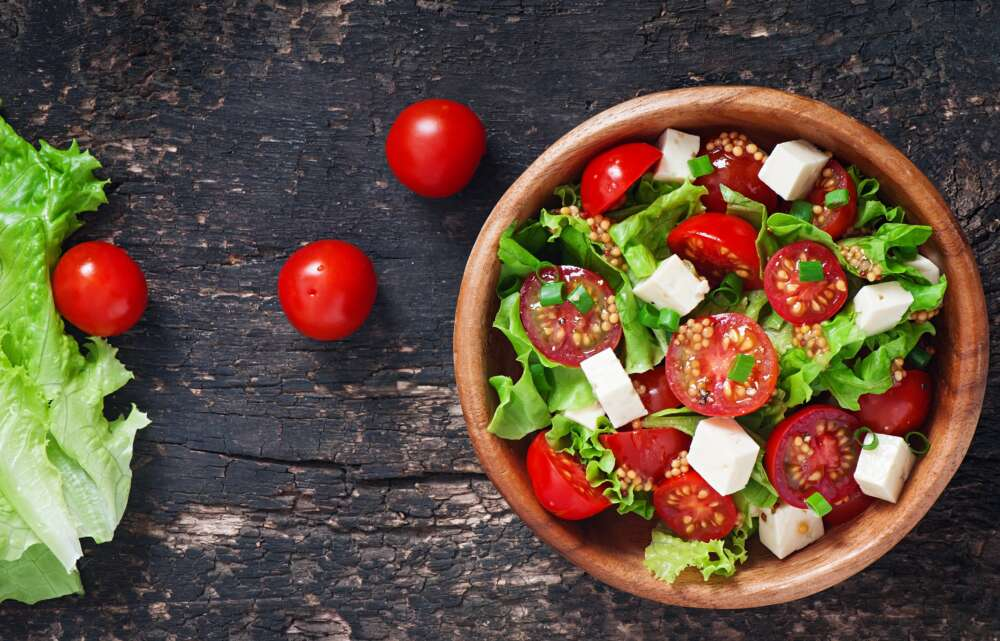 Tomato,Salad,With,Lettuce,,Cheese,And,Mustard,And,Garlic,Dressing.